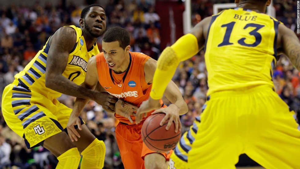 Michael Carter-Williams of Syracuse handles the ball against Jamil Wilson, left, and Vander Blue, right, of Marquette on March 30.
