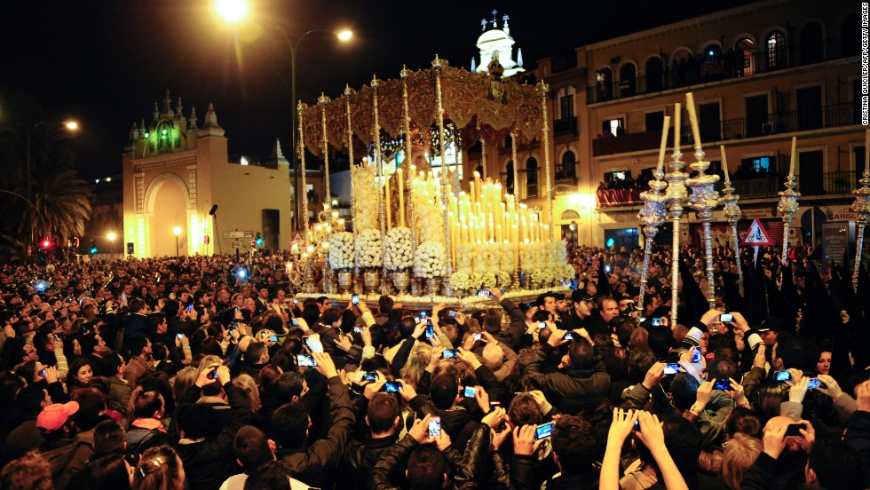 Believers gather around the Macarena Virgin during a procession in Seville, Spain, on Friday.
