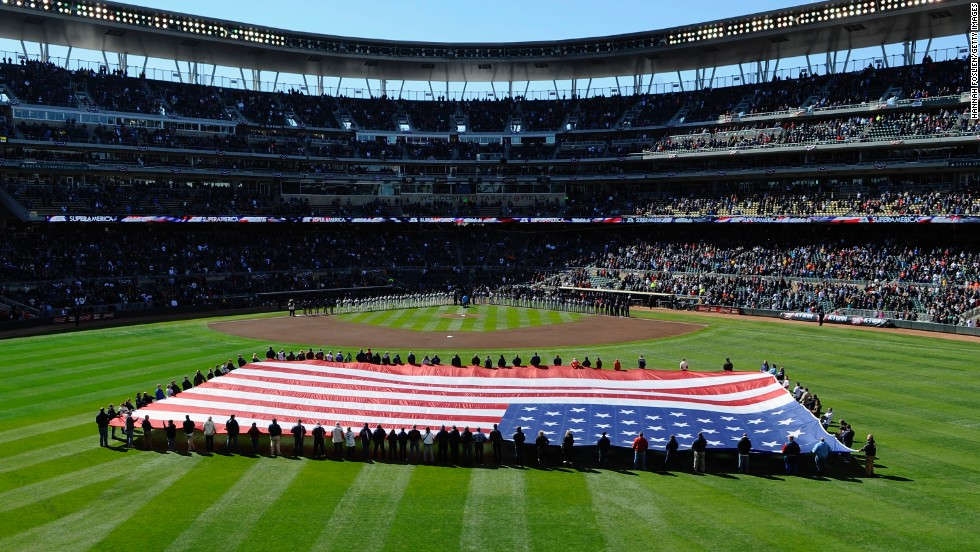 Players from the Twins and the Tigers stand along the baselines during the opening ceremony at Target Field.