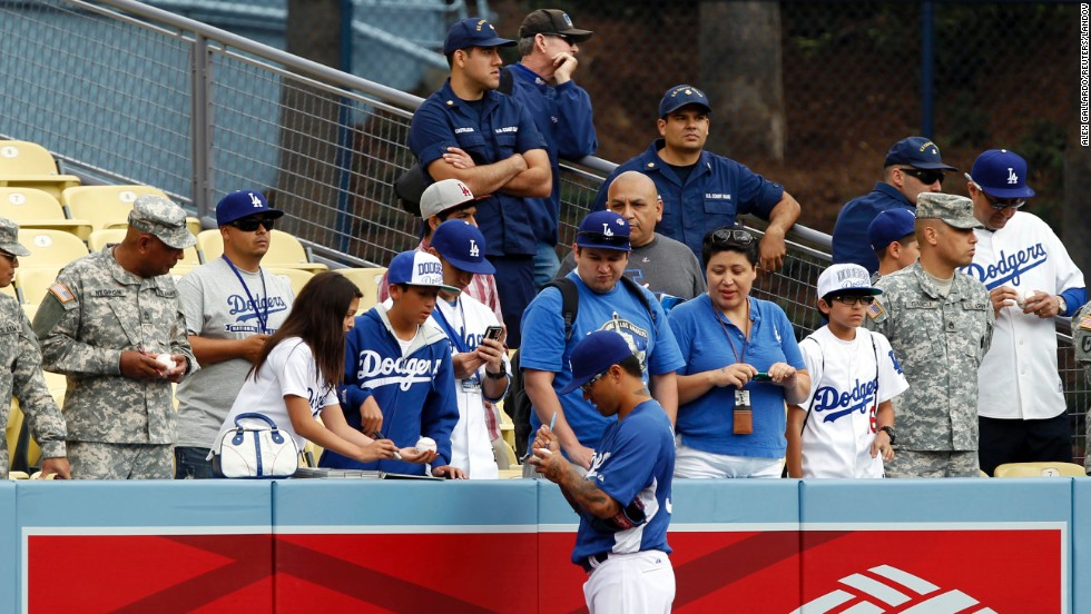 Dodgers relief pitcher Brandon League signs autographs during batting practice before taking on the Giants.