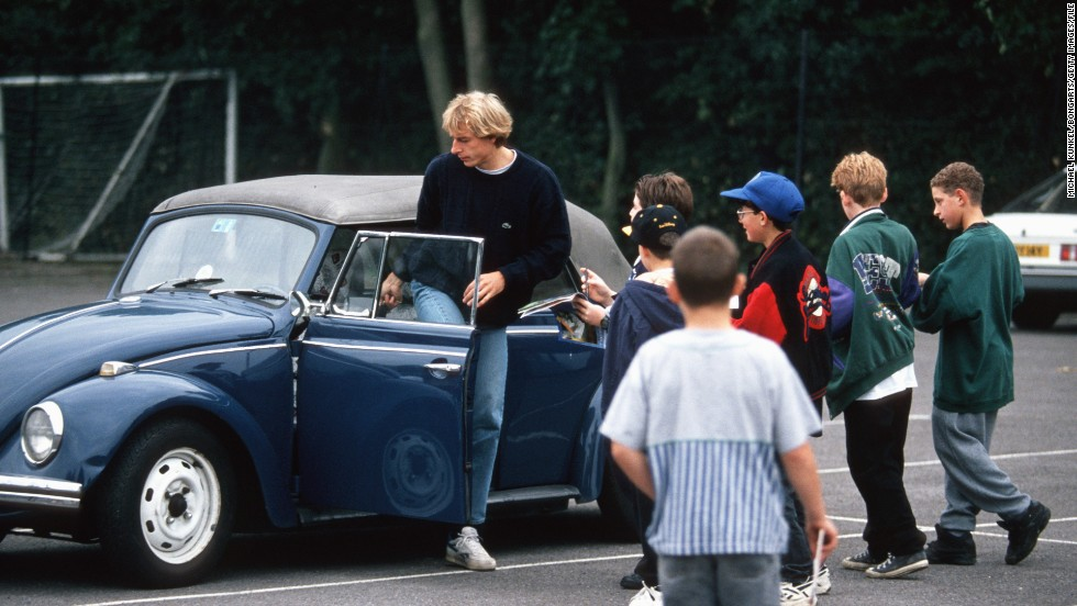 Former Germany star and current U.S. coach Jurgen Klinsmann gets into his Volkswagen Beetle while surrounded by onlooking schoolchildren.
