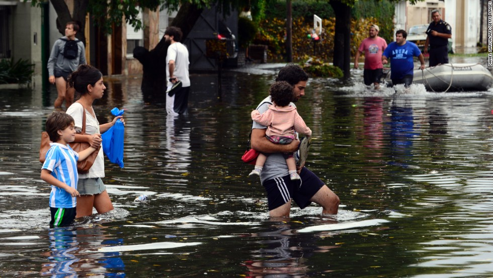 People wade through a flooded street after heavy rains in La Plata, Argentina, on Wednesday, April 3.