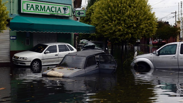 Partially submerged cars are seen outside of a pharmacy in La Plata on April 3.