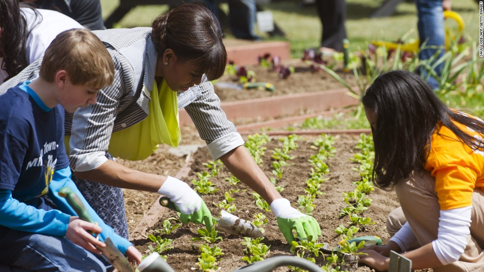 Nolan Deep of Milton, Vermont, left, and Kaila Bourne of Knoxville, Tennessee, help the first lady plant spinach.