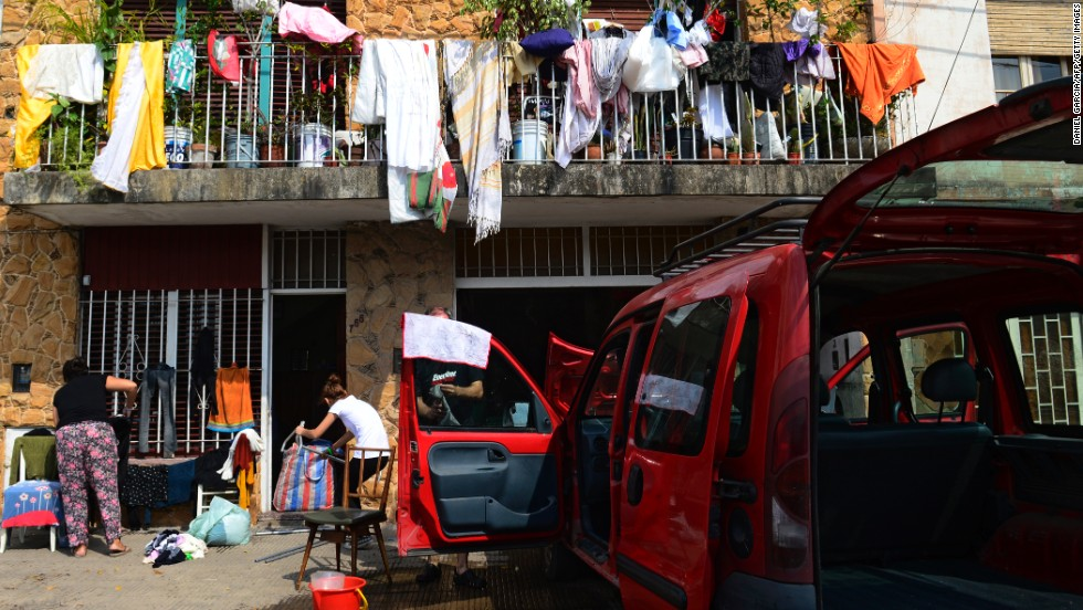 People affected by the storm and resulting floods in La Plata put clothes and other belongings out in the sun to dry on April 4. Rescuers were still searching for missing people.