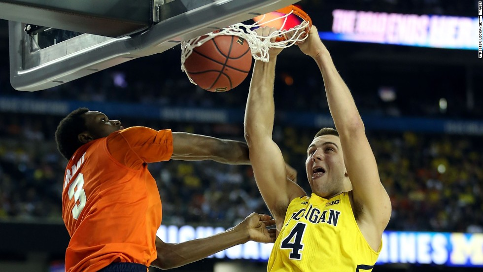 Mitch McGary of Michigan dunks against Jerami Grant of Syracuse.