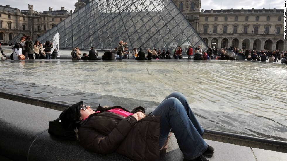 People enjoy sunny spring weather, a break from an unusually cold spring, near the Louvre Pyramid at the Cour Carree of the Louvre Museum on Sunday, April 7, in Paris.