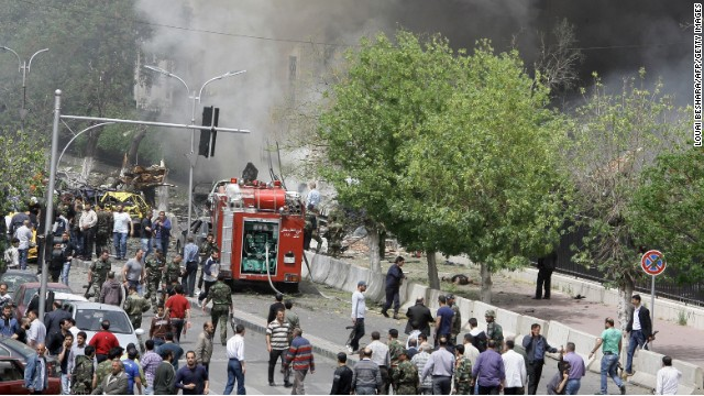 People inspect the scene of a deadly car bomb explosion which rocked central Damascus on April 8, 2013.