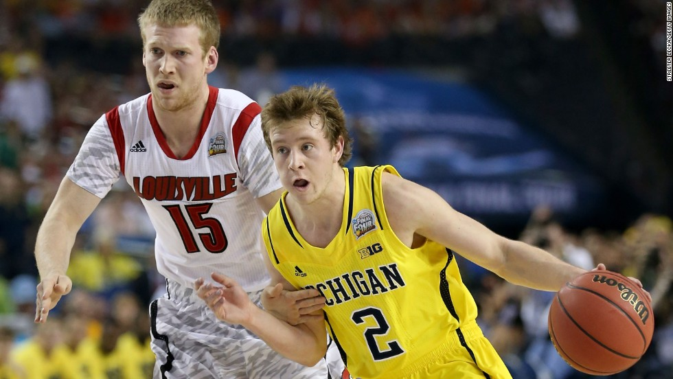 Spike Albrecht of the Michigan Wolverines drives against Tim Henderson of the Louisville Cardinals.