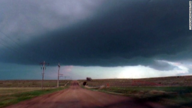 Ominous tornado darkens sky, touches down
