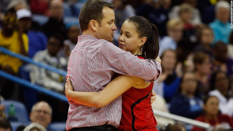 Head coach Jeff Walz of Louisville hugs Shoni Schimmel as she exits the game near the end of regulation against the Connecticut Huskies on April 9.