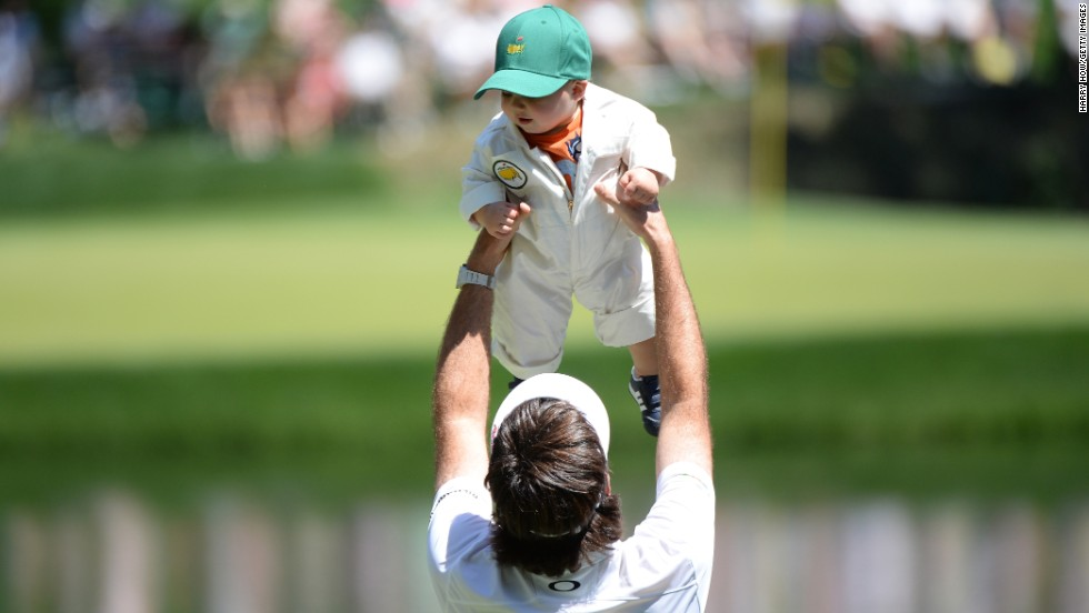 Bubba Watson of the U.S. lifts his son, Caleb, during the Par 3 Contest.