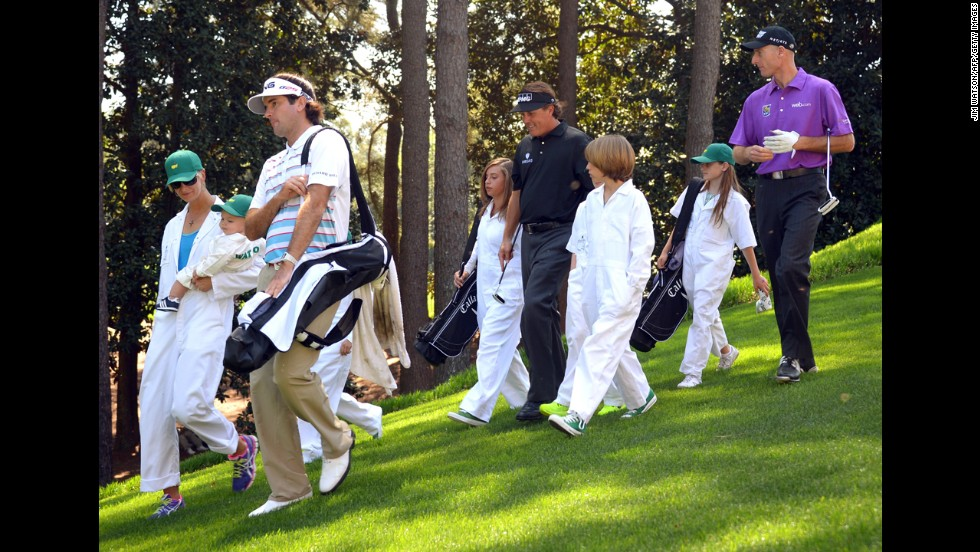 Bubba Watson, left, walks with his wife Angie and son Caleb, followed by Phil Mickelson, center, with kids Evan, Amanda, and Sophia and Jim Furyk, right, with daughter Caleigh.