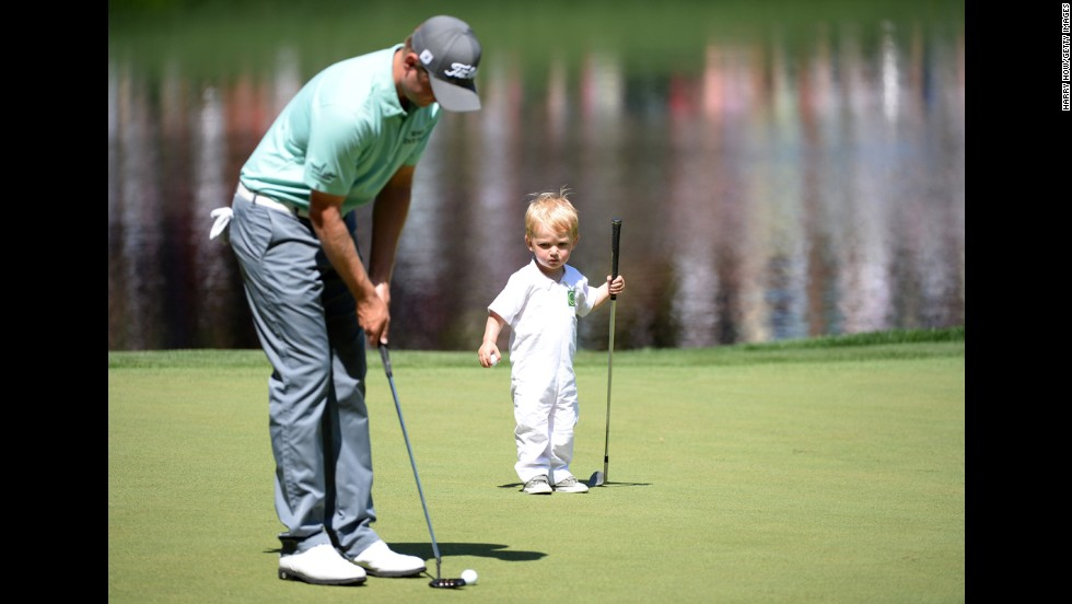 John Merrick of the U.S. putts as his son, Chase, watches.
