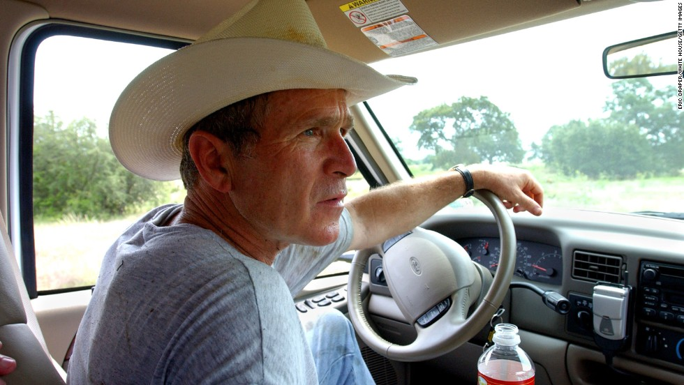 President George W. Bush dresses for the location as he drives his pickup at his ranch in Crawford, Texas, in 2002.