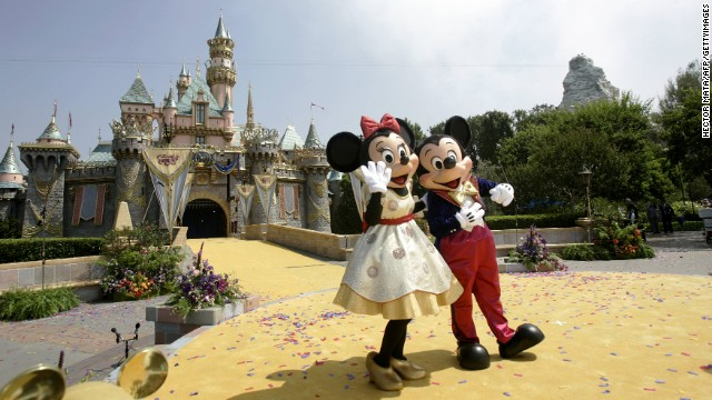 Disney characters Mickey Mouse and Minnie wave to a crowd of people in front the Sleeping Beauty Castle during the 50th anniversary of the opening of Disneyland  in Anaheim, California, 17 July 2005. California's Governor Arnold Schwarzenegger, Disney CEO Michael Eisner, his designated successor Robert Iger and other personalities attended the event. AFP PHOTO/Hector MATA        (Photo credit should read HECTOR MATA/AFP/GettyImages)