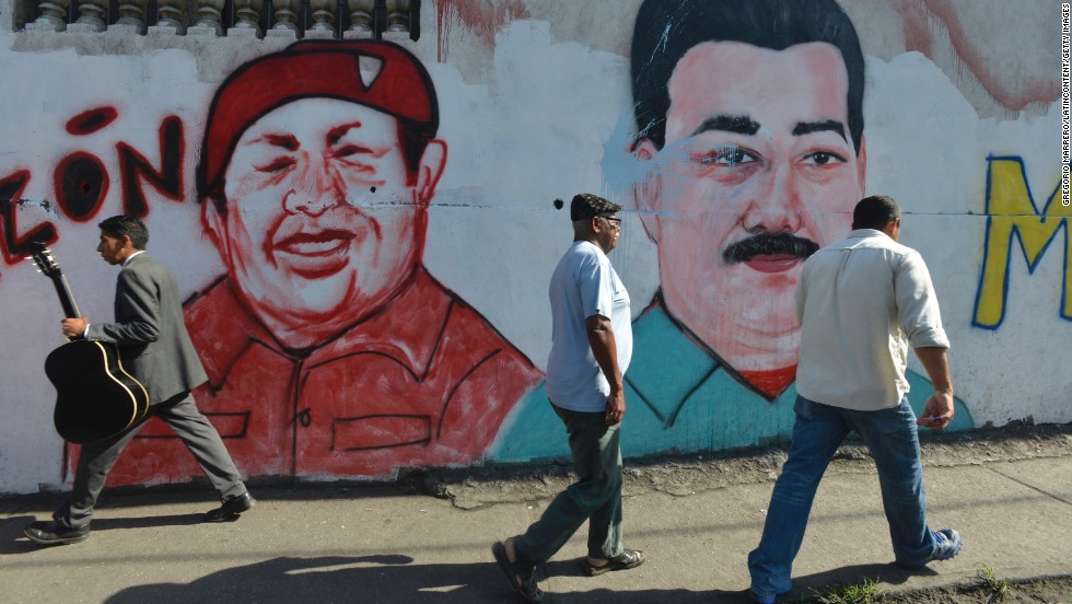 People walk past murals with Hugo Chavez's and Maduro's likenesses in Caracas.