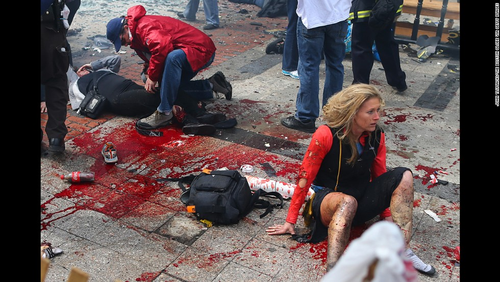 Victims lie on the ground at the scene of the first explosion.