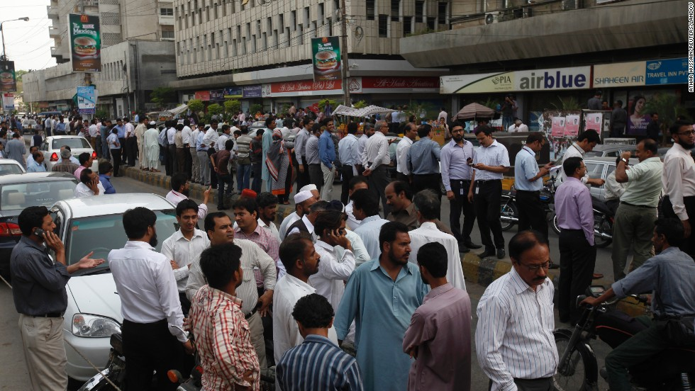 People stand outside their office buildings on Tuesday in Karachi.