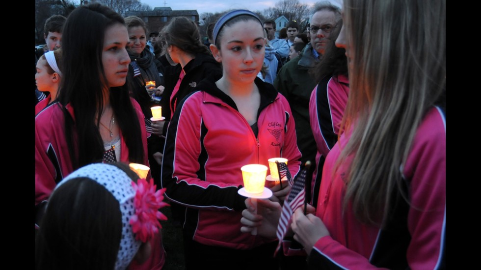 Students from the Clifden Academy hold an American flag and candles during a vigil in Dorcester, Massachusetts, on April 16, 2013.
