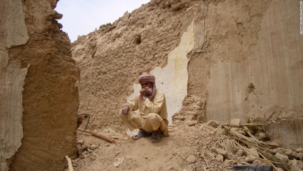 A Pakistani man sits on the remains of his mud house in Mashkell on Wednesday.