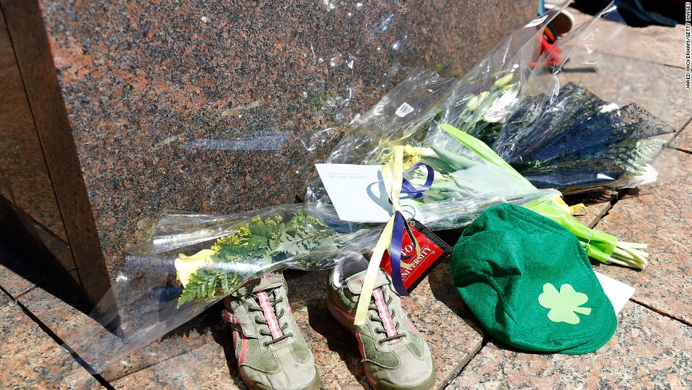 Flowers, running shoes and other items are left in memory of bombing victim Lingzi Lu.