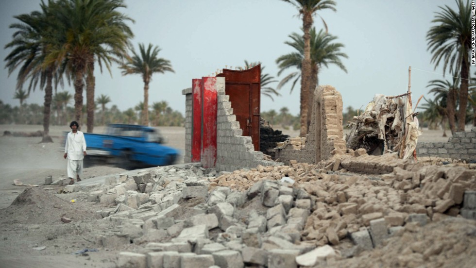 An earthquake survivor walks past a collapsed house in the Mashkell area of Pakistan's Baluchistan province on Thursday, April 18. The casualty count from an earthquake that struck near Pakistan's border with Iran stands at 35 dead and more than 150 injured, authorities said Wednesday.
