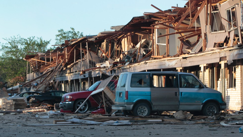 The remains of an apartment complex lie on cars.
