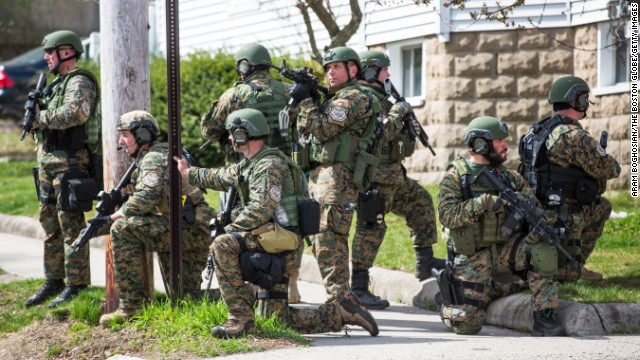 Swat team members gather as they continue to search neighborhoods in Watertown, Massachusetts on Friday.