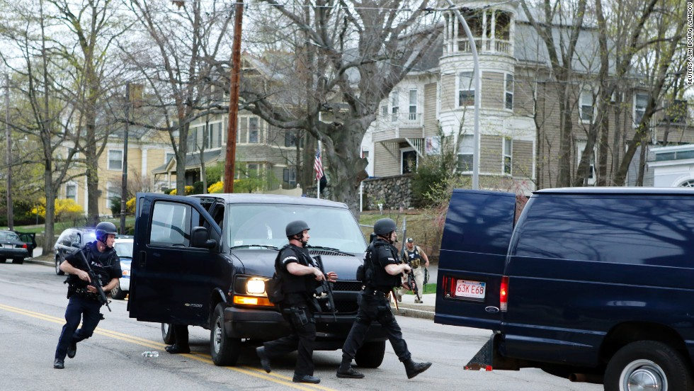 SWAT team members run toward a police assault on a house as gunfire erupts on April 19.