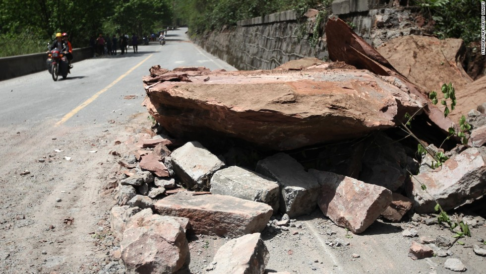 Huge rocks lie on a road in Longmen on Saturday.