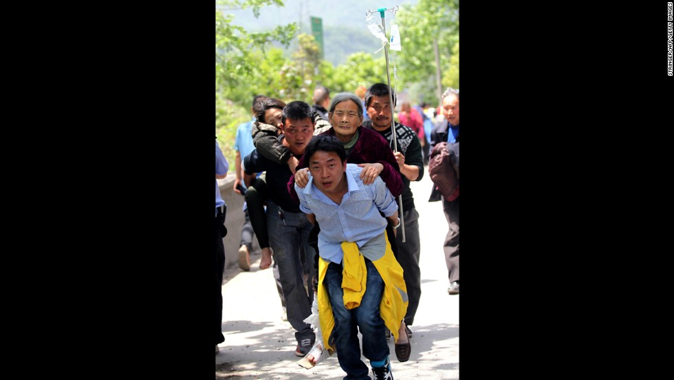 Residents help carry injured people to the hospital on Saturday in the city of Ya'an.