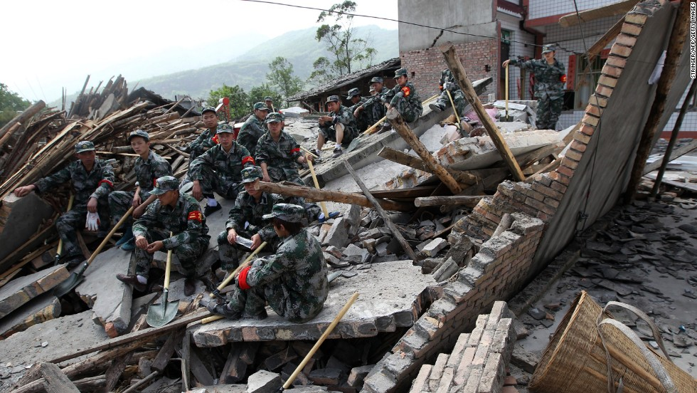 Rescuers sit on ruins of a house in Longmen, an area close to the epicenter of the earthquake.