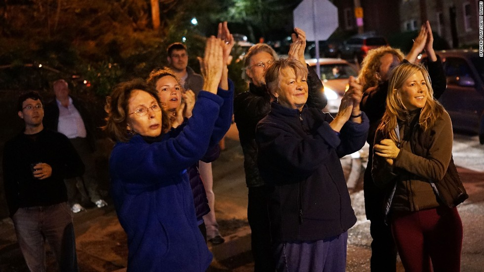 Women cheer police as they exit Franklin Street on Friday, April 19, in Watertown, Massachusetts.