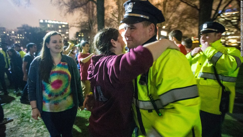 A woman gives a Boston police officer a hug and other officers are thanked during a celebration in the Boston Common on April 19.