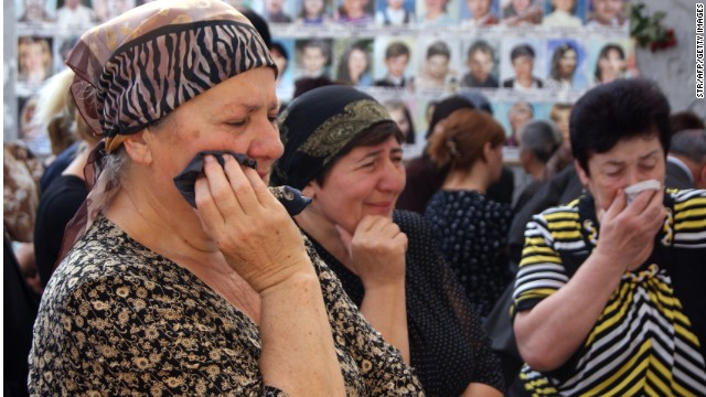 Russians cry inside the Beslan school gym remembering when at least 300 kids and parents were killed by Chechen rebels in 2004.
