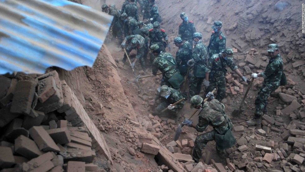 Rescuers dig through rubble in quake-hit Qingren township in southwest China's Sichuan Province on Saturday, April 20.