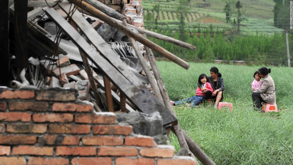 Residents rest near destroyed houses in Sichuan Province on Saturday.