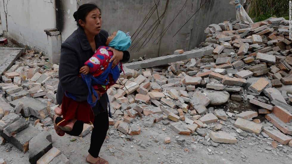 A woman carries her baby through rubble in Lushan County in Sichuan, China, on Sunday, April 21.