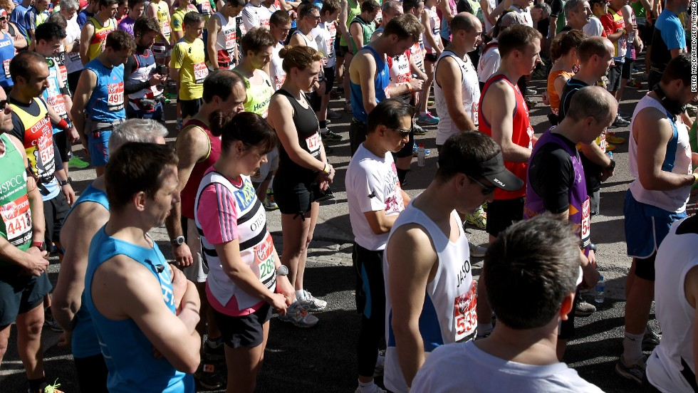 Runners stand in a silent tribute to the victims of the Boston Marathon bombings before the start of the London Marathon from Greenwich Park on April 21, 2013 in London, England.