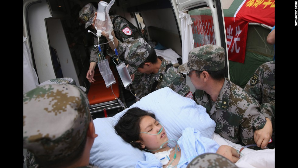 Military medical officers carry a patient to an ambulance at the hospital in Ya'an, China, on Monday.