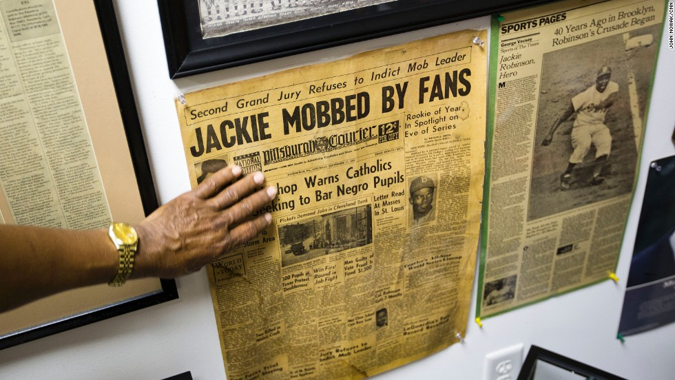 Hadley points out a front-page story in black-owned Pittsburgh Courier about Jackie Robinson, who became a Brooklyn Dodger in 1947.