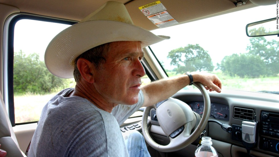 George W. Bush drives his pickup truck at his ranch in Crawford, Texas, in August 2002.