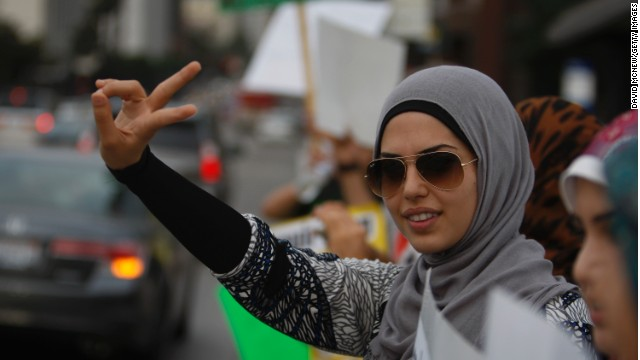 A woman makes a peace sign gesture at a protest in Los Angeles, California, against religious hatred.