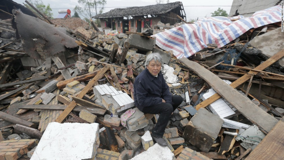 A woman sits on debris in Ya'an on Tuesday, April 23.