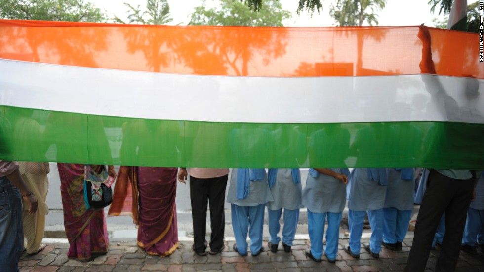 Indian youths stand in front of a banner with the colors of their national flag in a silent demonstration in Hyderabad on April 23.