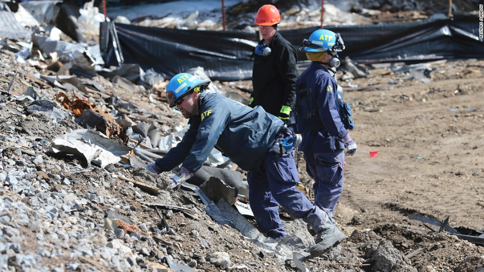 Agents from the Bureau of Alcohol, Tobacco, Firearms and Explosives search the bank of rail tracks for evidence at the site of the explosion.