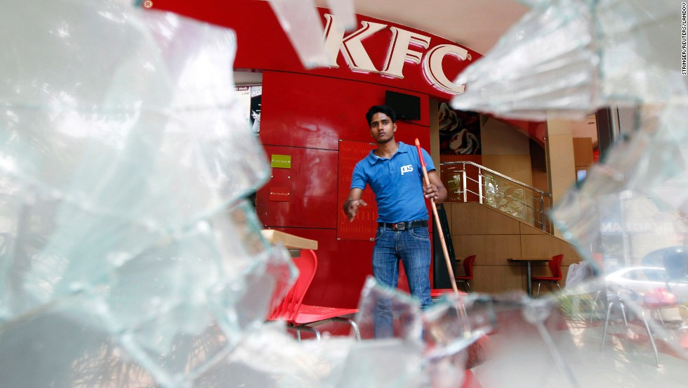 A man cleans up a restaurant after protesters broke its windows.