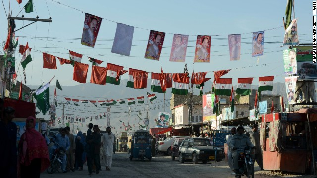 Commuters pass under the flags and posters of political parties in Quetta, Pakistan, on Sunday.