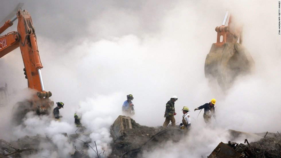 Firefighters make their way over the ruins through clouds of smoke at ground zero on October 11, 2001.